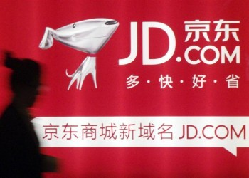 A woman walks past a advertisement board of Jingdong Mall (JD.com) in Nanjing, Jiangsu province in this May 7, 2013 file photo. REUTERS/China Daily/Files