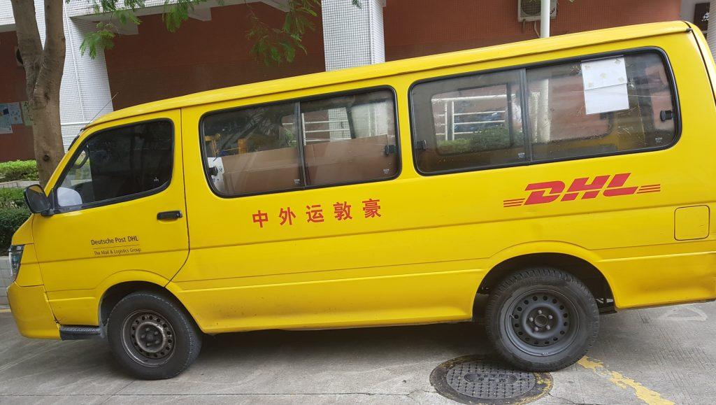 parkender gelber dhl van in china vor einem wohngebäude