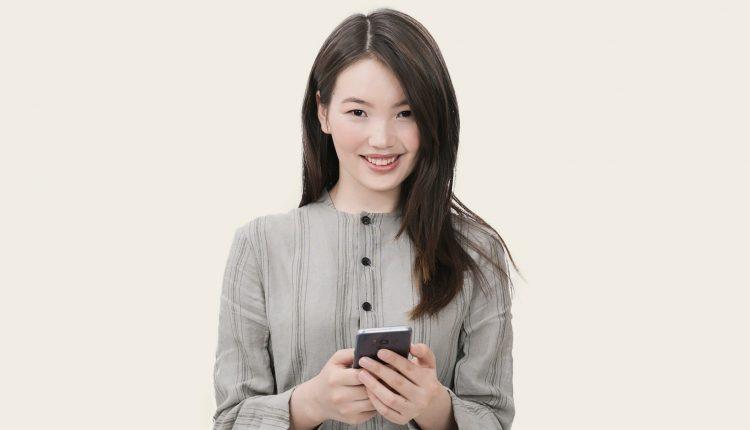 erwachsene chinesin mit smartphone